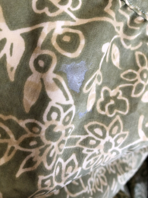 green and beige fabric with a silver paint stain